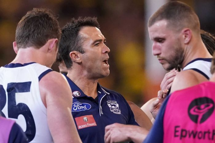 An AFL coach gives his players instructions in a preliminary final at the MCG.