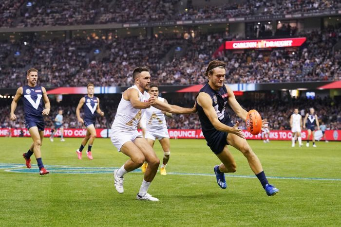 An AFL player in a charity match gets ready to kick the ball as his opponent tries to grab him.