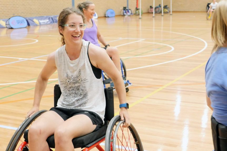 A woman in a wheelchair on a basketball court smiles .