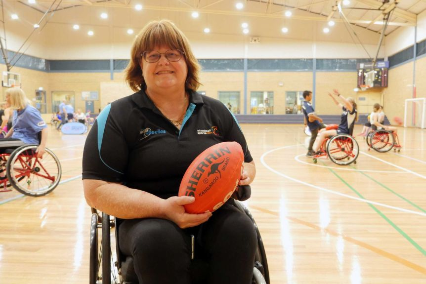 A woman in a wheelchair holds an Aussie Rules football.
