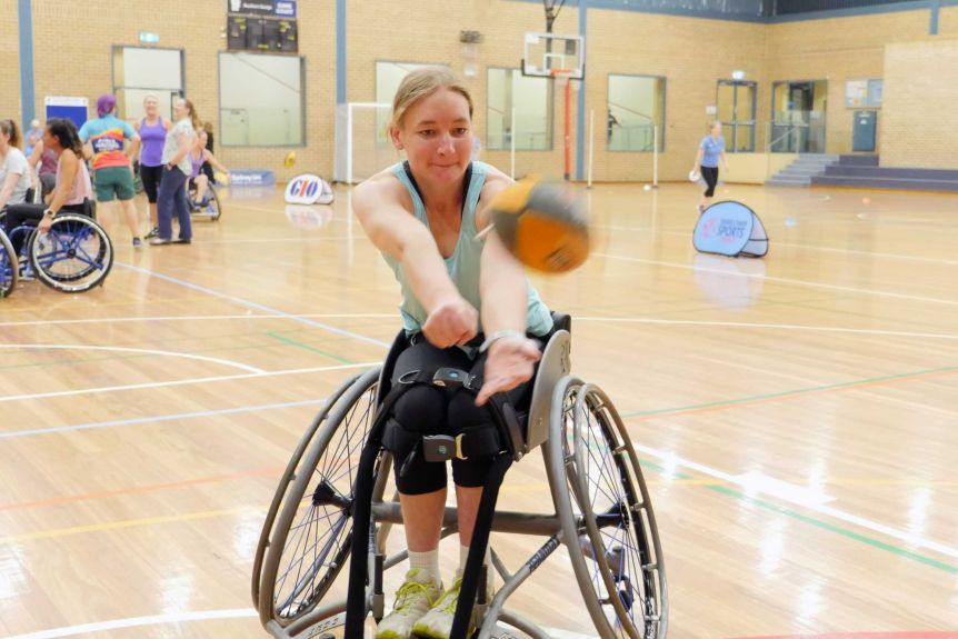 A woman handballs a football from a wheelchair while on a basketball court.